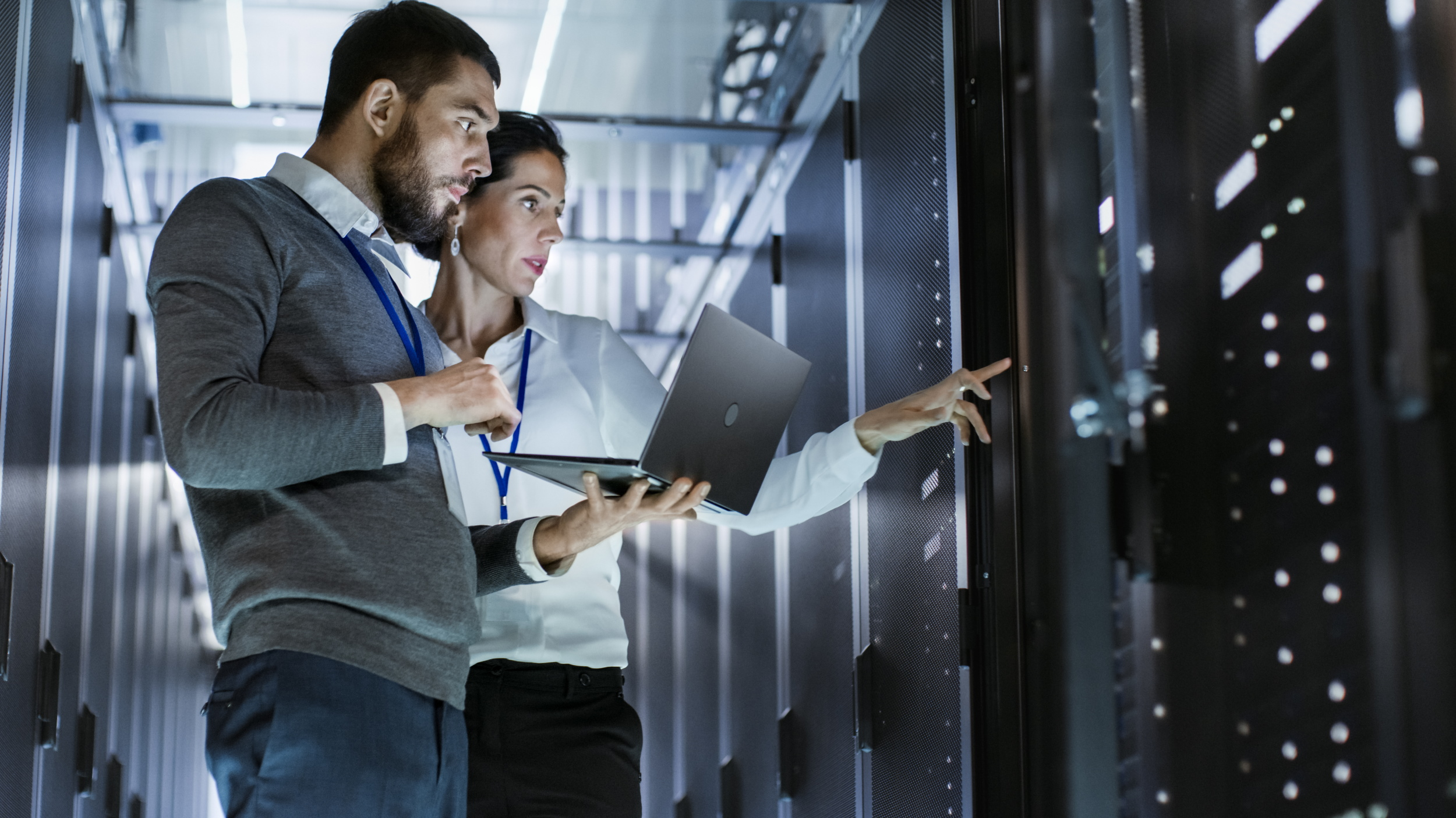 Two engineers dealing with network management issues at a server rack in a data center