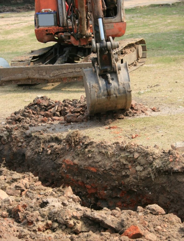 Backhoe digging a large trench, putting underground communication lines at risk.